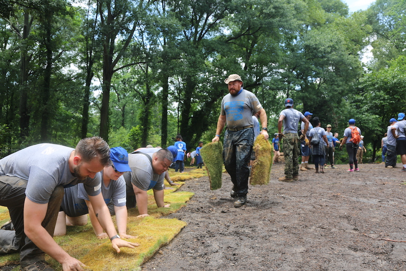 Crew and Ambassadors work together at Mass Deployment 2017, Operation Westside Surge to lay sod to transform an empty space into a welcoming park for residents near the Atlanta Beltline Trail.