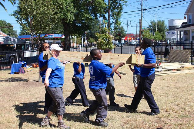 Volunteers carry wood at Democracy Prep in Washington, DC, September 11, 2015. Photo credit: GREG CALLAN, DEMOCRACY PREP PUBLIC SCHOOLS