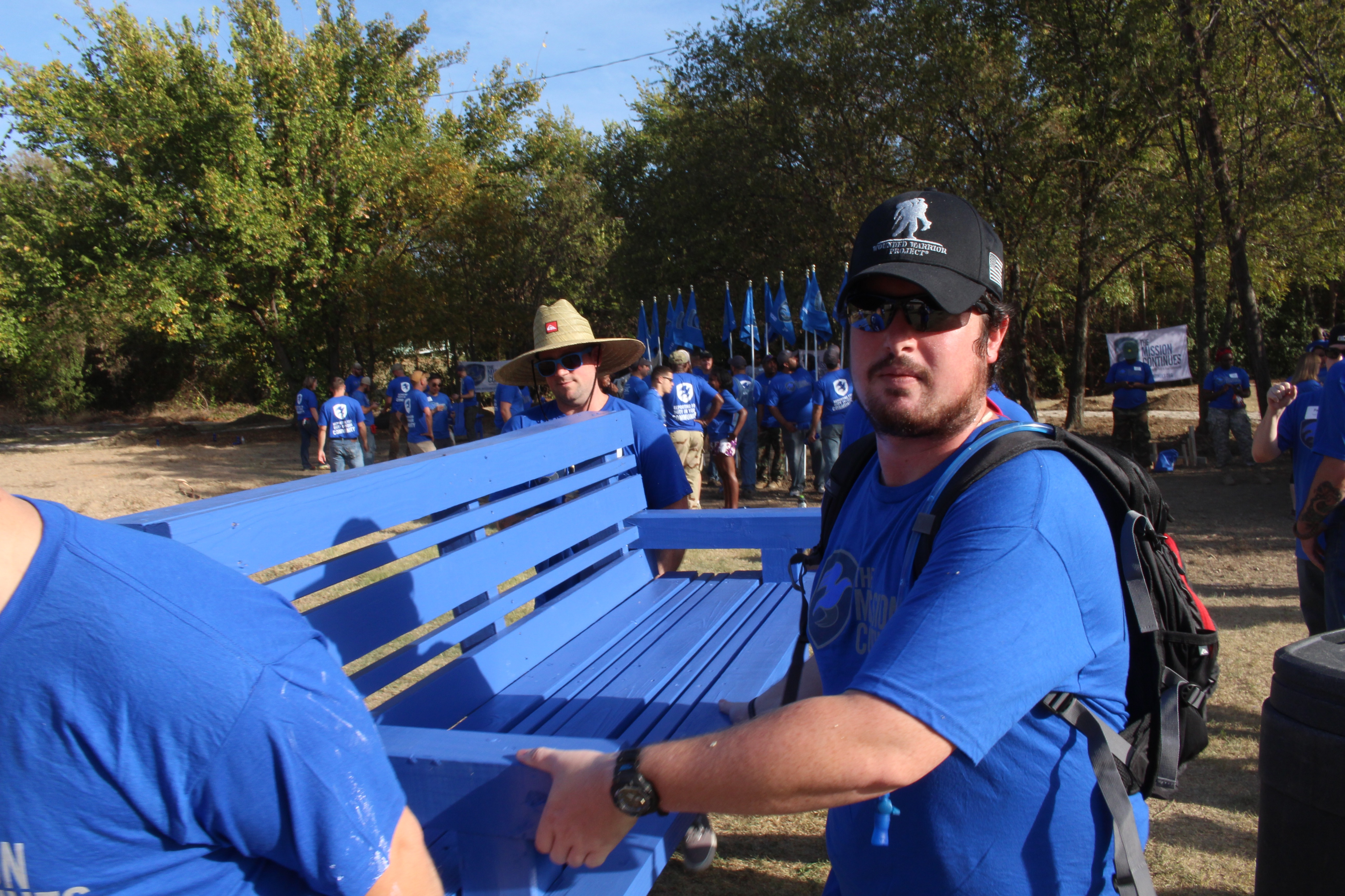 A new Fellow and Wounded Warrior Project alum install a freshly painted bench.