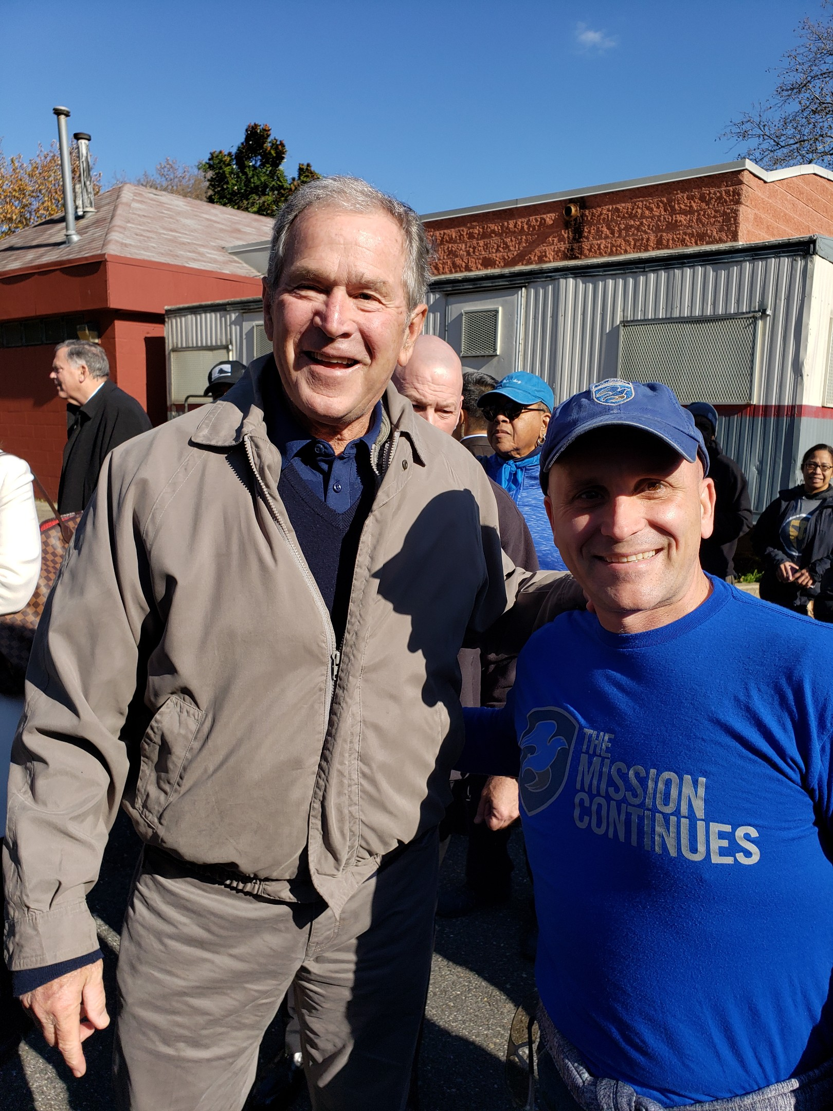 Former President George W. Bush dropped by a service project in Philadelphia, and poses for a photo with Platoon Leader Anthony Fedele.